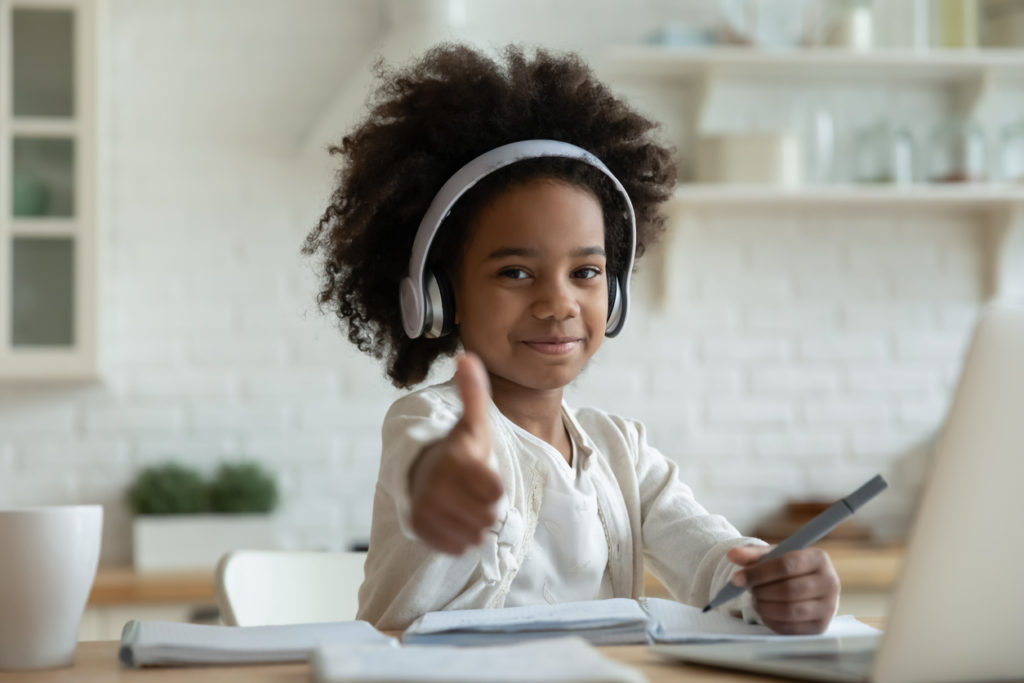 African-girl-in- headphones-enjoy-e-learn-sit-at-table- showing-thumbs-up- recommend-virtual-school